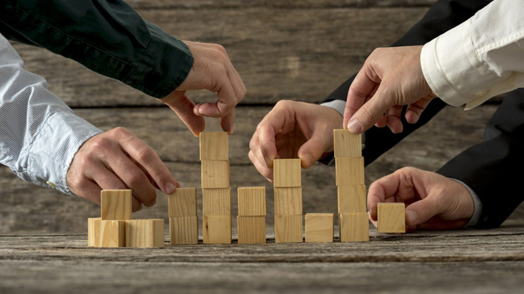 Hands of five businessman holding wooden blocks placing them into a structure. Conceptual of teamwork, strategy and business start up.