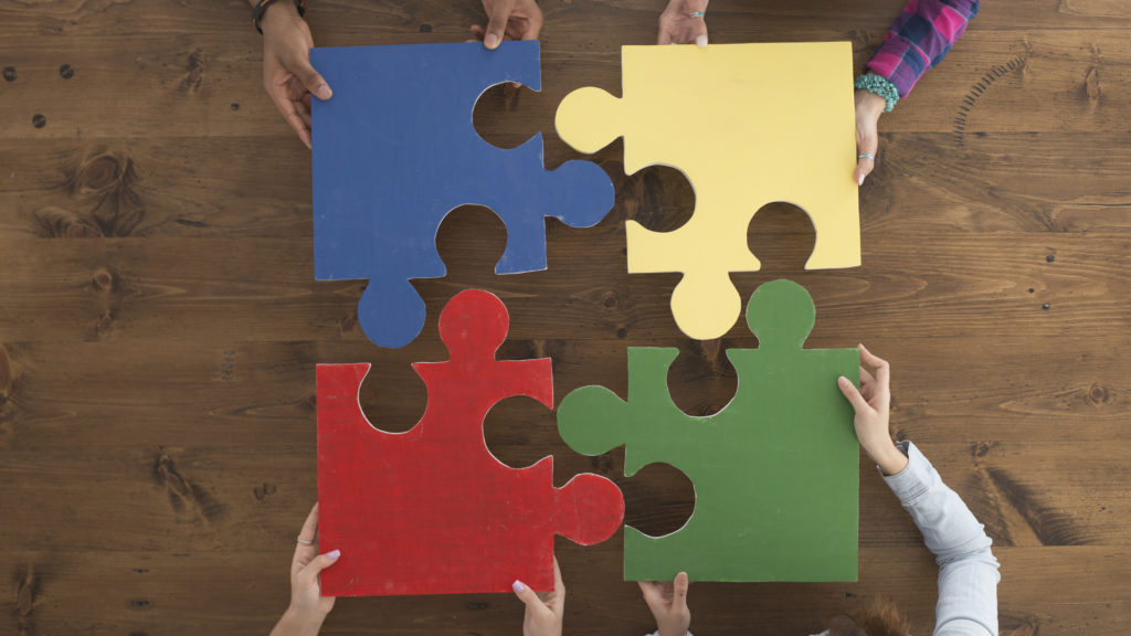 A multi-ethnic group of college age students are putting together large puzzle pieces.