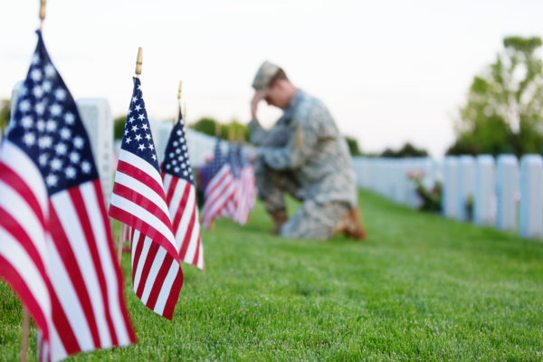 American soldier kneeling at a veterans grave on memorial day. Focus on the foreground.