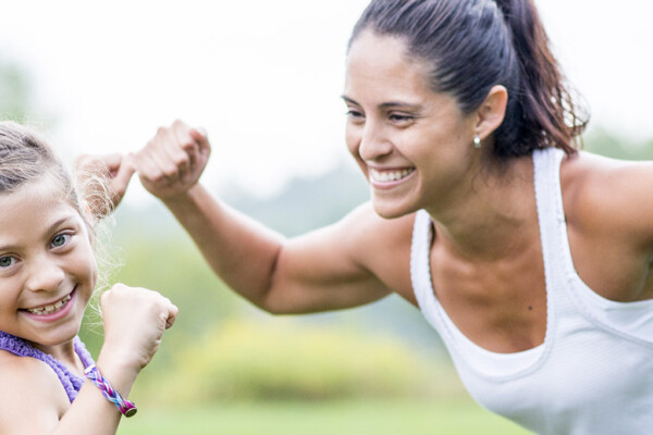 A mother and daughter are outdoors in a field. They are wearing casual athletic clothing. They are flexing their muscles together.
