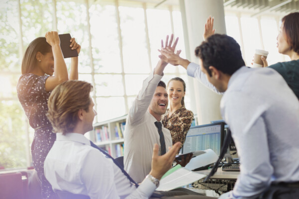 Business people high-fiving and celebrating in office