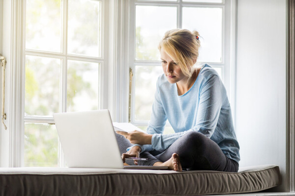 A full length photo of woman using laptop while holding documents at home. Young female is sitting on window sill. She is working from home.