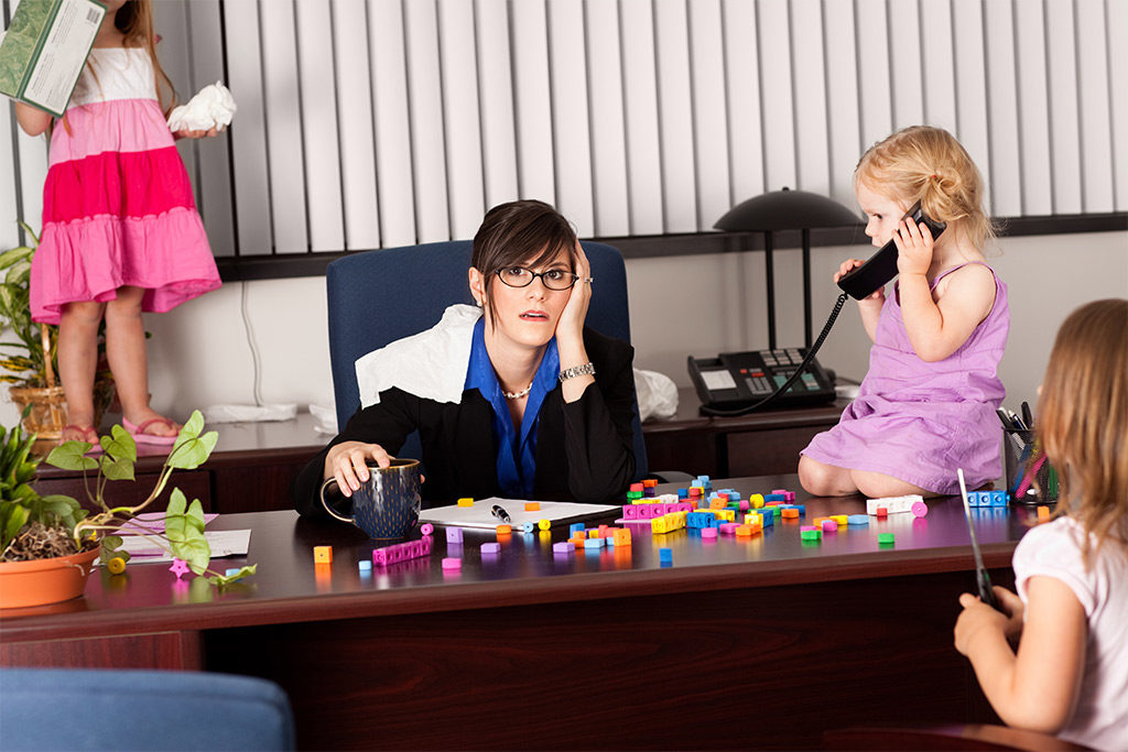 Mother Working with children playing around her at desk