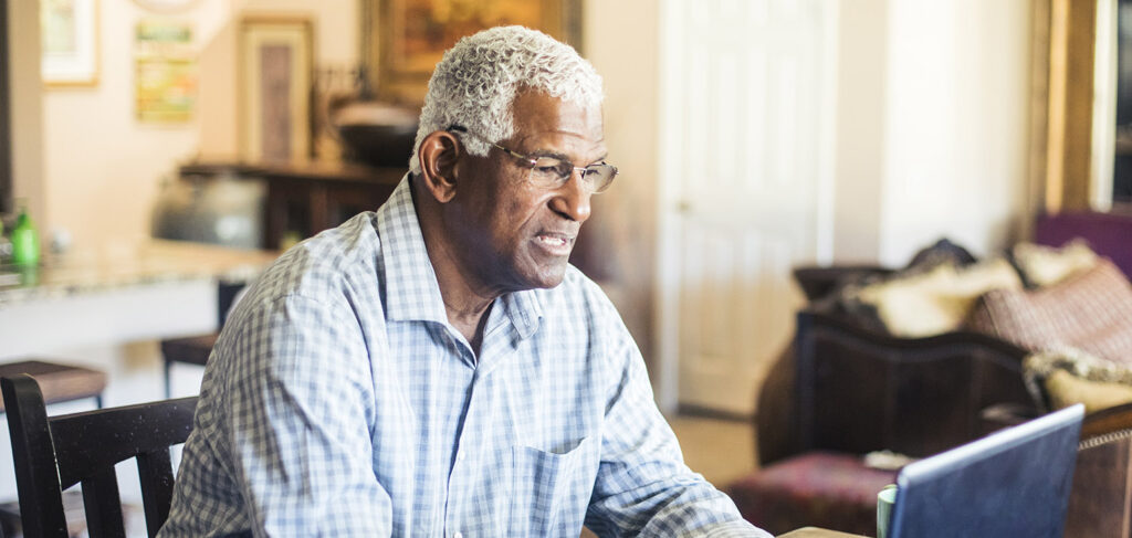A senior black man works from his computer at home