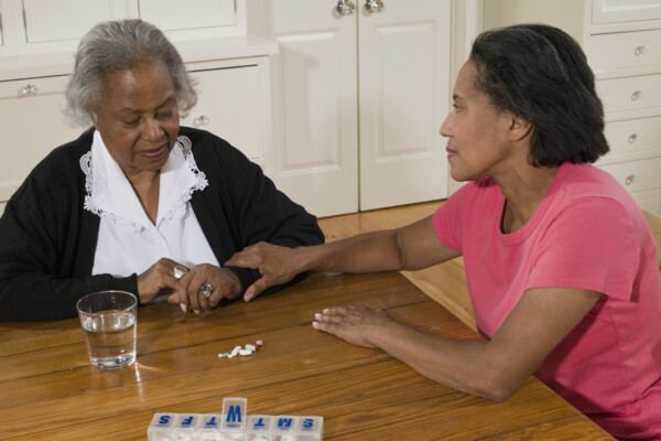 Senior woman with daughter sitting at table with pill boxes